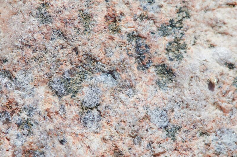 The surface of the chipped granite stone, rough, unpolished with multicolored splashes, natural, not treated, as a background for. The surface of the chipped royalty free stock photo