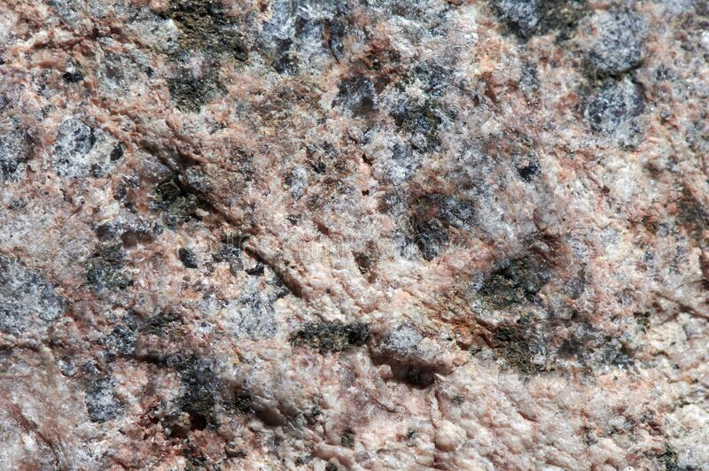 The surface of the chipped granite stone, rough, unpolished with multicolored splashes, natural, not treated, as a background for. The surface of the chipped stock images