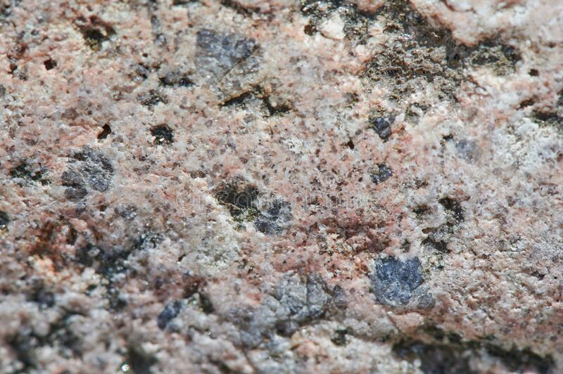 The surface of the chipped granite stone, rough, unpolished with multicolored splashes, natural, not treated, as a background for. The surface of the chipped stock photos