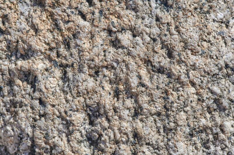 The surface of the chipped granite stone, rough, unpolished with multicolored splashes, natural, not treated, as a background for. The surface of the chipped royalty free stock image