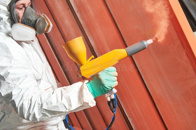 Polymer coating of metal detail with powder spraying gun stock photos