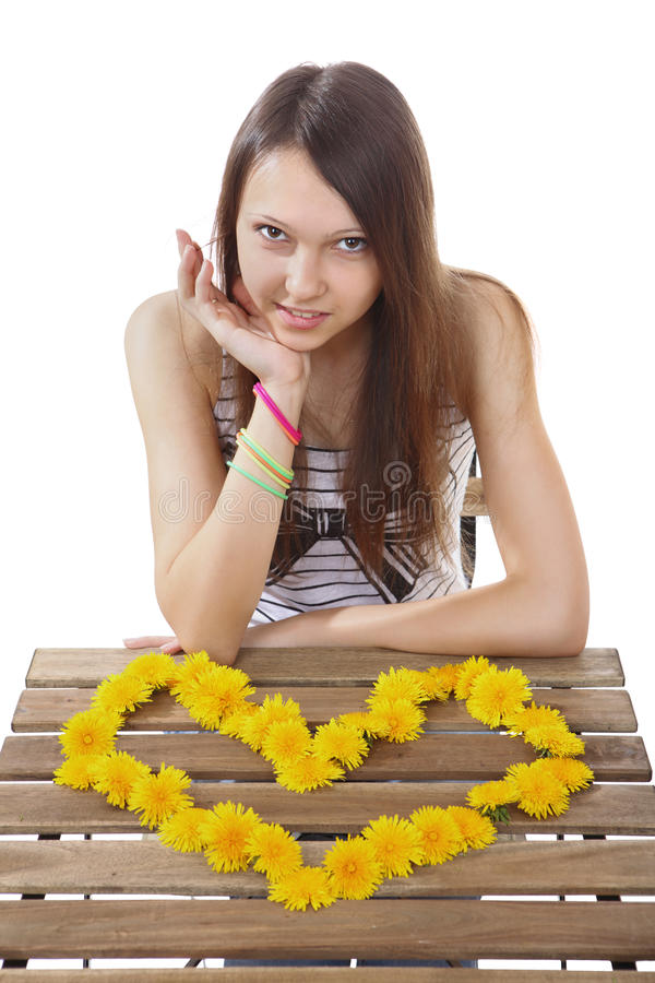 Teen girl 15 years old, made of yellow flowers valentine. One girl brunette teen Caucasian, 15 years old, sitting at a table on which is lined with heart stock image