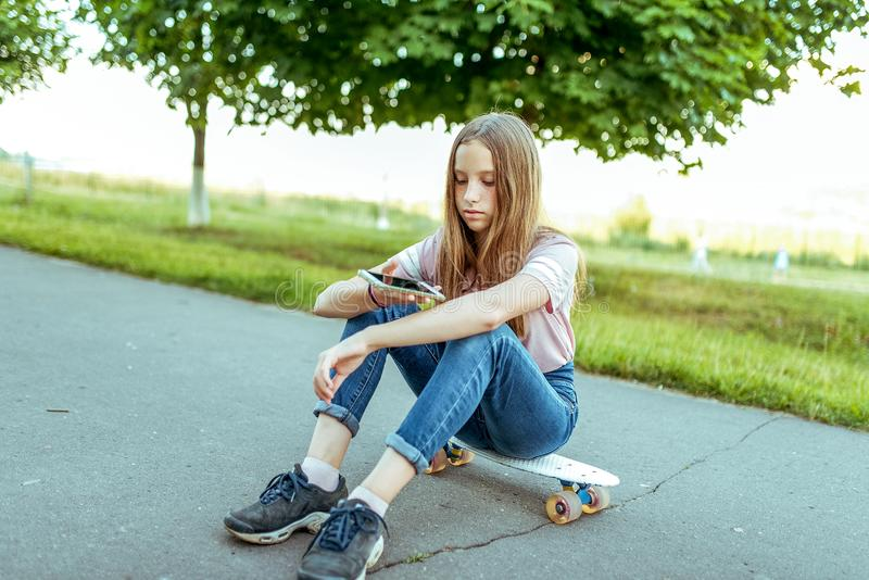 Teen girl 11-14 years old, sitting in hands of skate. In summer city in casual jeans and pink T-shirt. Communication in. Teen girl 9-15 years old, sitting in royalty free stock photos