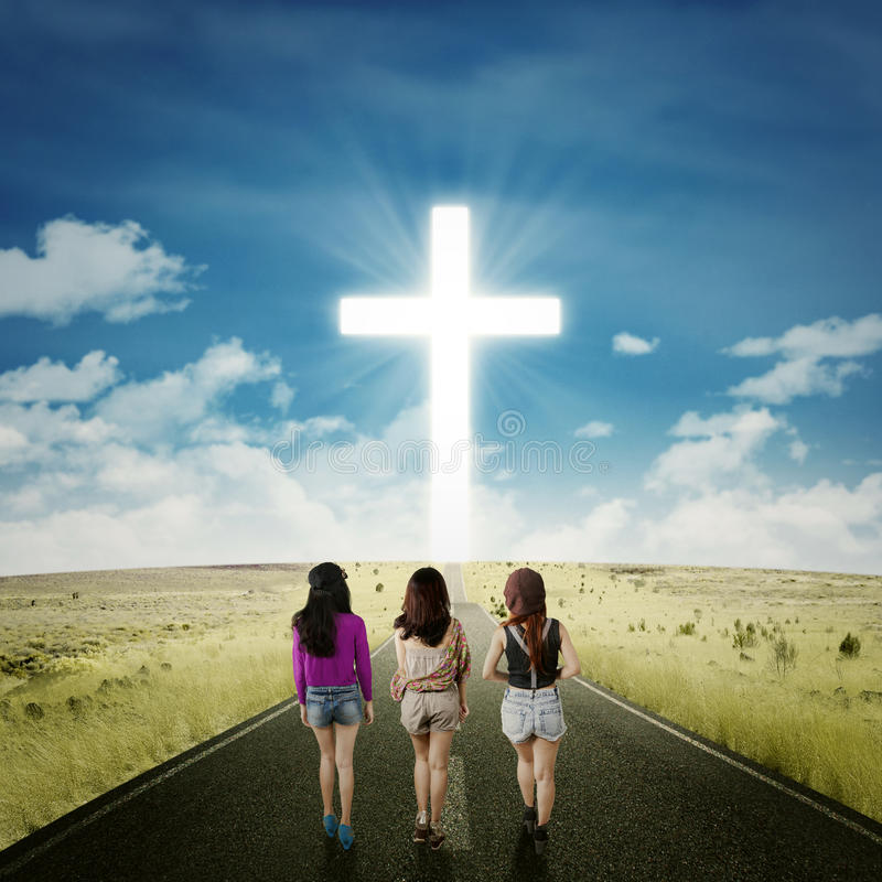 Teenager girls on the road with a cross stock photos