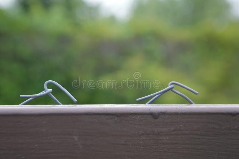 Tensioning and securing a mesh fence with a metal wire netting. Tensioning and securing a mesh fence with a the metal wire netting stock photos