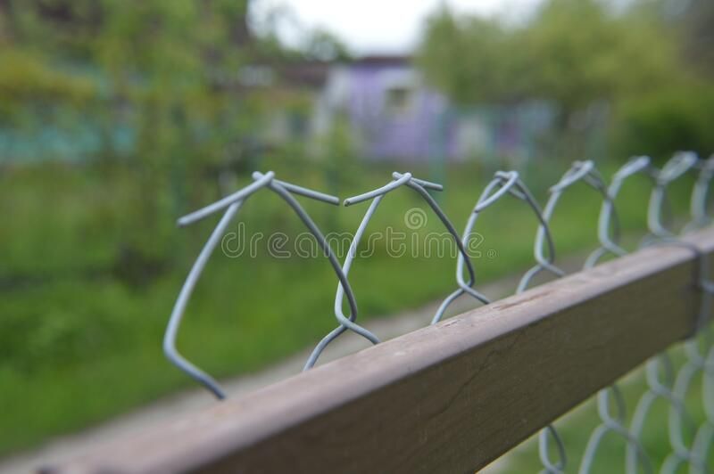 Tensioning and securing a mesh fence with a metal wire netting. Tensioning and securing a mesh fence with a the metal wire netting royalty free stock images