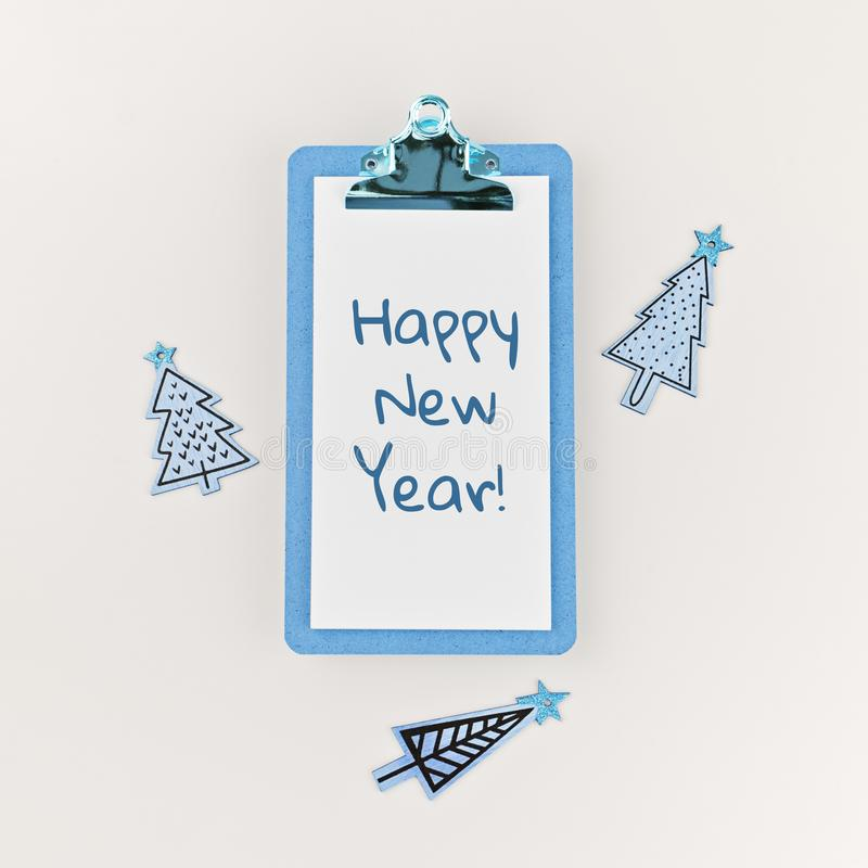 Text happy New Year on clipboard and wooden funny Christmas trees royalty free stock photo