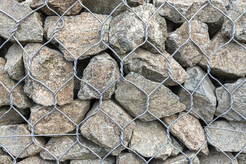 Textural background - granite stone behind a mesh netting, wall.  stock images