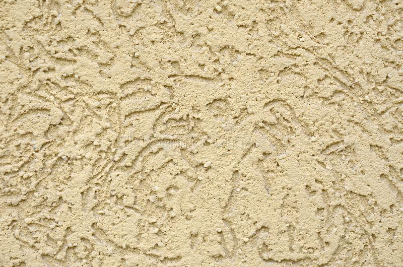 The texture of the beige decorative plaster in bark beetle style. Russian variation of decorating facade walls stock image