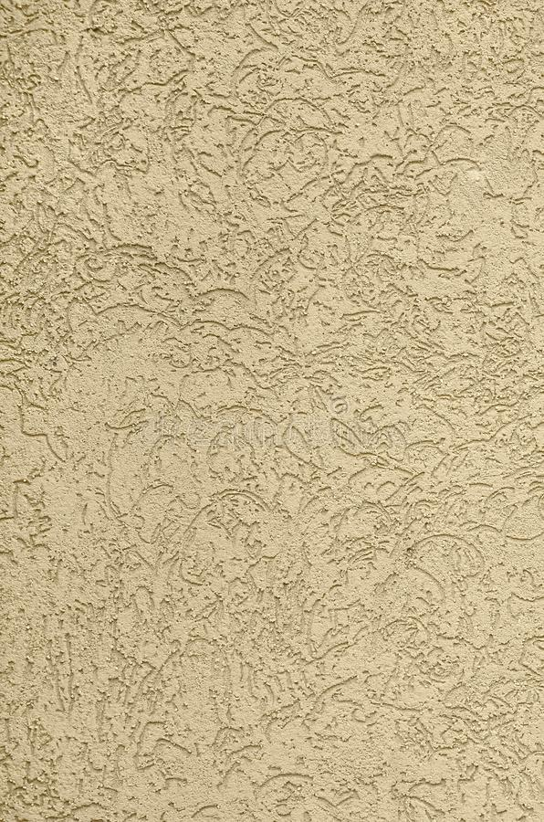 The texture of the beige decorative plaster in bark beetle style. Russian variation of decorating facade walls stock photos