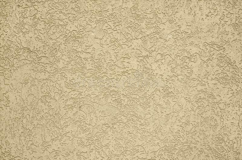 The texture of the beige decorative plaster in bark beetle style. Russian variation of decorating facade walls stock photo