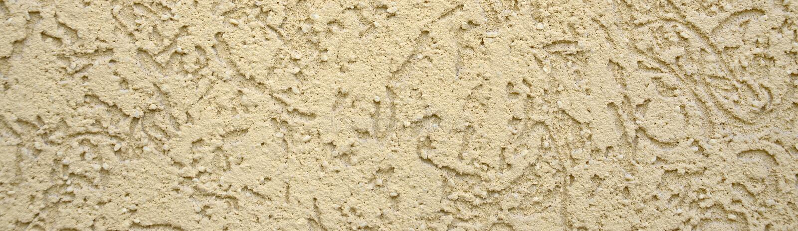 The texture of the beige decorative plaster in bark beetle style. Russian variation of decorating facade walls stock photography