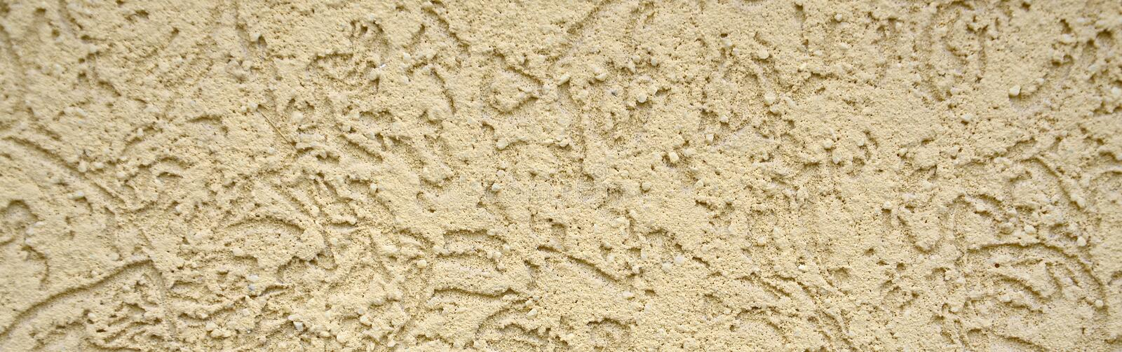 The texture of the beige decorative plaster in bark beetle style. Russian variation of decorating facade walls stock images