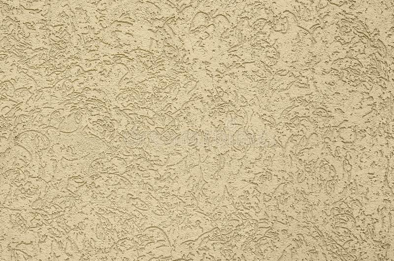 The texture of the beige decorative plaster in bark beetle style. Russian variation of decorating facade walls royalty free stock images