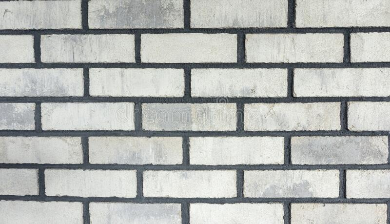 The texture of the facing bricks is white with a rough black grout for mocap. Photo of a wall lined with white bricks in the loft. Stylish texture of the facing stock photos
