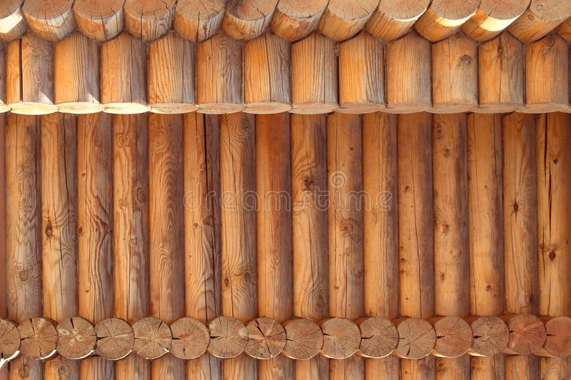 Texture parallel folded treated timber. Ancient technology building of Russian log hut, wood house cottages and churches. Texture in parallel folded logs. The royalty free stock photo