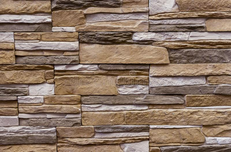 Texture of the stone wall. Panel of stones for finishing the facade of the building and interior design of the house. Background. For design and decoration royalty free stock photo