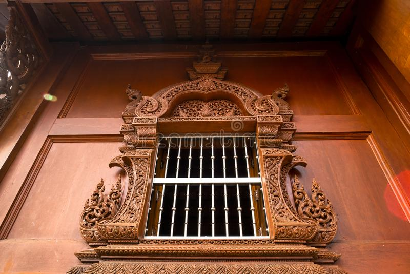 Thai style wooden building with beautiful carved window frame at a Buddhist temple in Thailand. royalty free stock photos