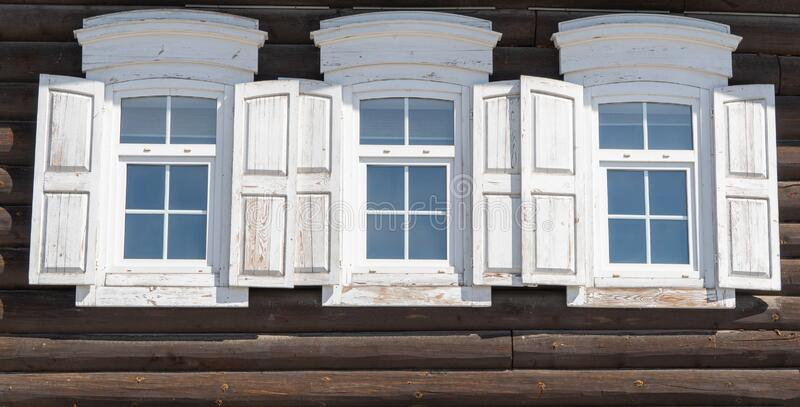 Three old wooden Windows with open shutters. Old Russian country style royalty free stock image