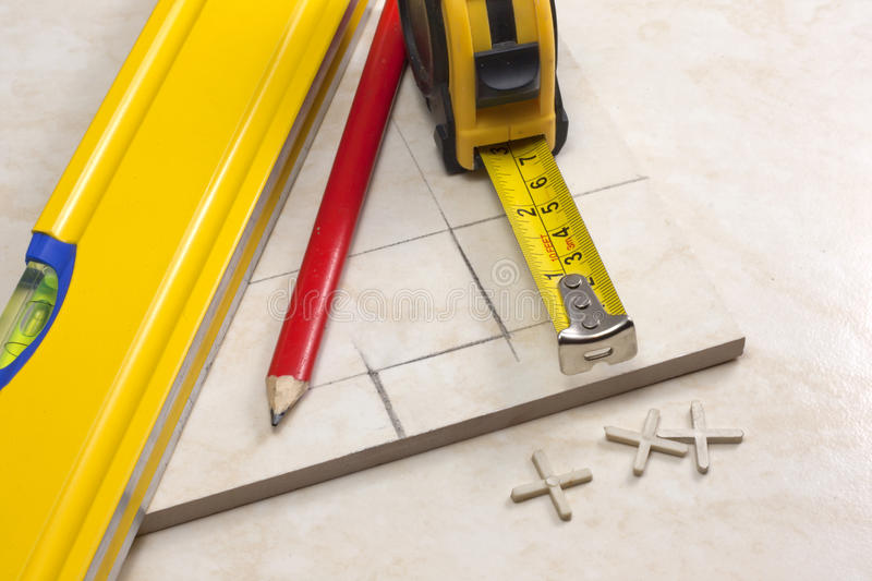 Tiler preparation for cutting tiles. Tiler is measured accurately tile before cutting in his own work place royalty free stock image