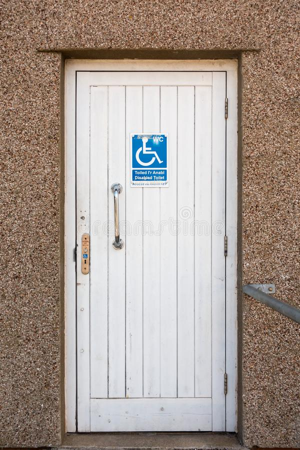 Toilet Door with Disabled Sign. White wooden door of a public toilet with a disabled sign stock images