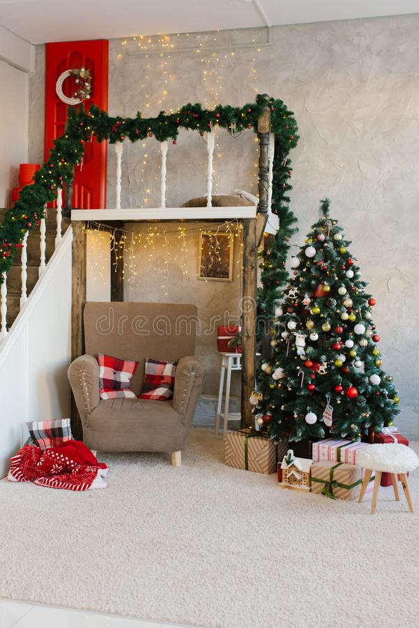 Traditional classic Christmas tree and beige armchair, stairs to the second floor in the living room or dining room. In the house stock photo