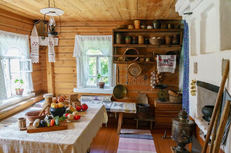 Traditional Russian cottage with oven and crockery. Interior of a peasant hut royalty free stock images
