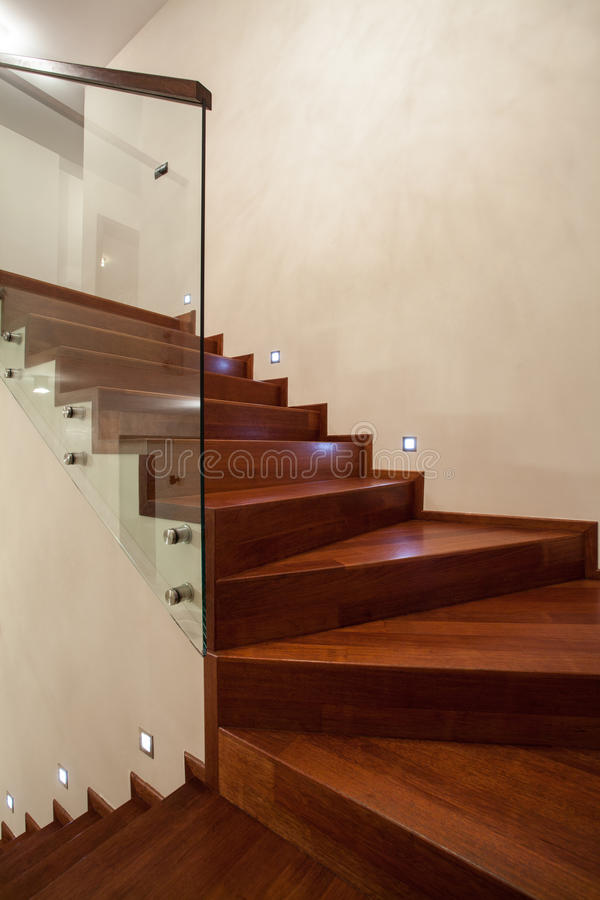 Travertine house- Closeup of wooden, glass stairs. In modern interior royalty free stock photos