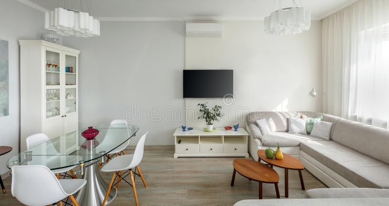 Trendy designed dining and living rooms in white lagom Scandinavian style. Elegant contemporary loft apartment concept stock image