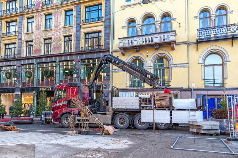A truck driver unloads building materials to the ground using a built-in crane royalty free stock photo