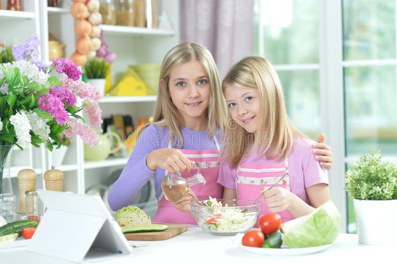 Two girls in aprons preparing fresh salad royalty free stock photography