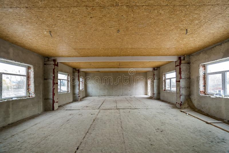 Unfinished apartment or house big loft room under reconstruction. Plywood ceiling, plastered walls, window openings, cement floor. Construction and renovation royalty free stock photography