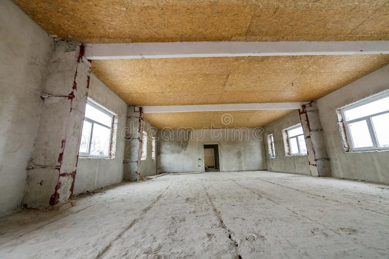 Unfinished apartment or house big loft room under reconstruction. Plywood ceiling, plastered walls, window openings, cement floor. Construction and renovation royalty free stock photo