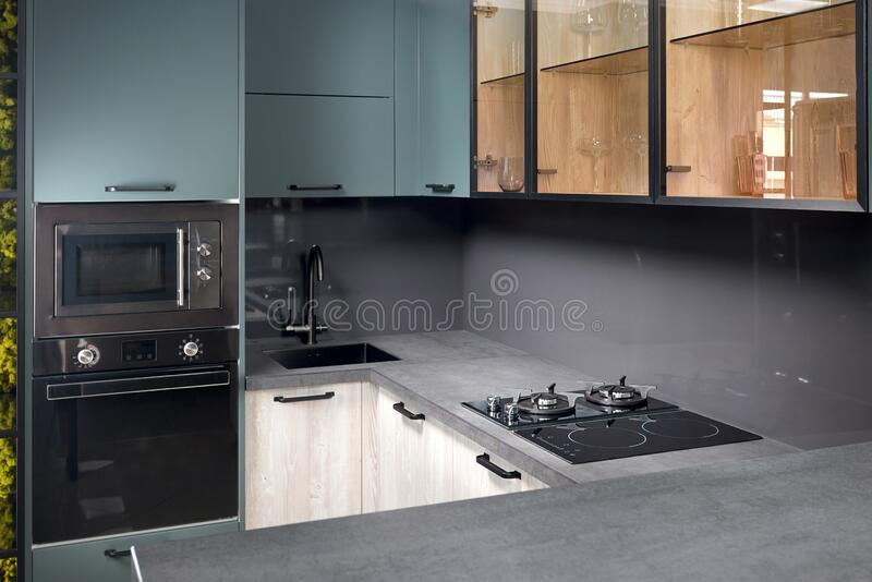 Upscale Aqua Menthe kitchen in luxury home with hob induction electric microwave oven flat wooden panels design ceramic. Upscale Aqua Menthe kitchen in luxury royalty free stock photography