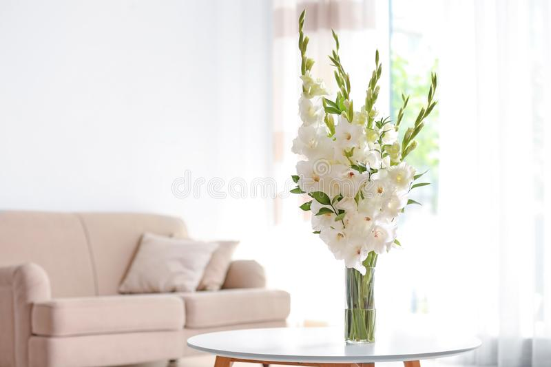 Vase with beautiful white gladiolus flowers on wooden table in living room royalty free stock photography