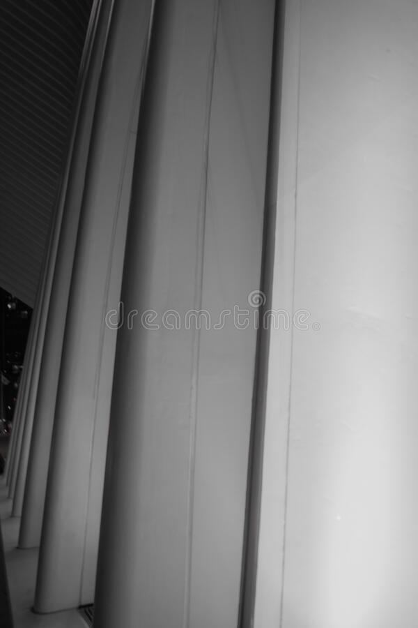 Vertical greyscale shot of a modern architectural structure with concrete columns stock images