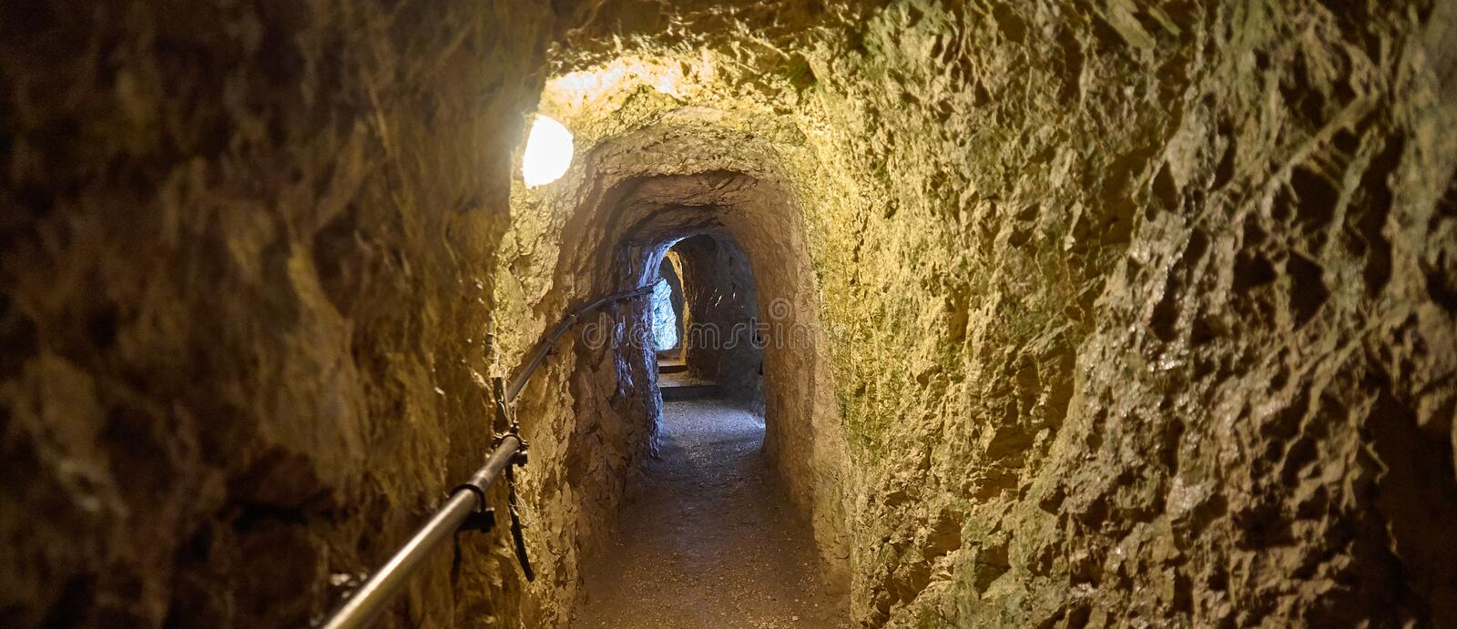 View through a narrow tunnel in the mountains made of limestone with an electric lamp on the ceiling royalty free stock photo