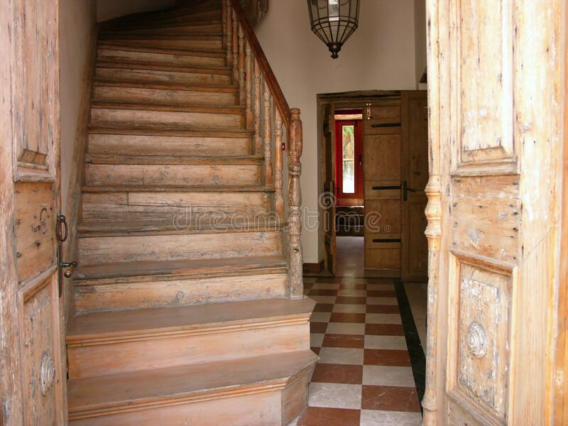 View of an open door with a wooden staircase inside the house stock image