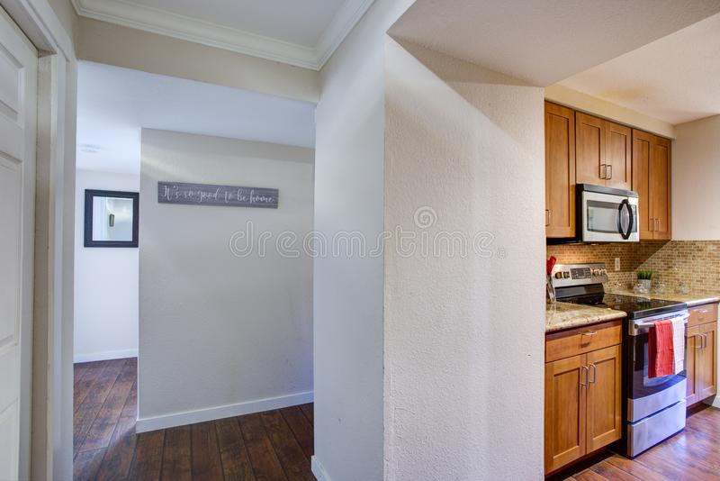 View of Small galley kitchen design from the white hallway stock photo