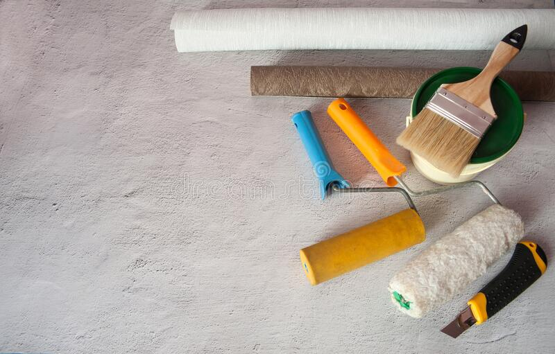 Wallpaper and rollers for gluing, painting tools and paint cans. royalty free stock photos