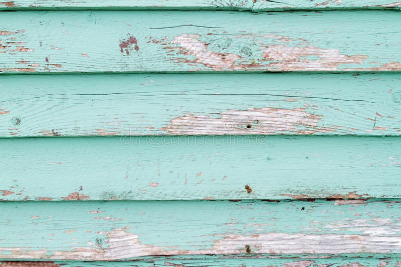 Weathered clapboard background. Old weathered clapboard with green paint and damaged wood stock photo