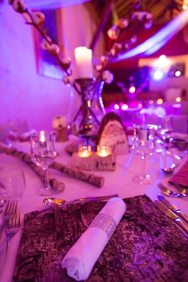 Wedding Table Decoration and Napkin on Wood Bark Mat. In Purple Lighting stock photo