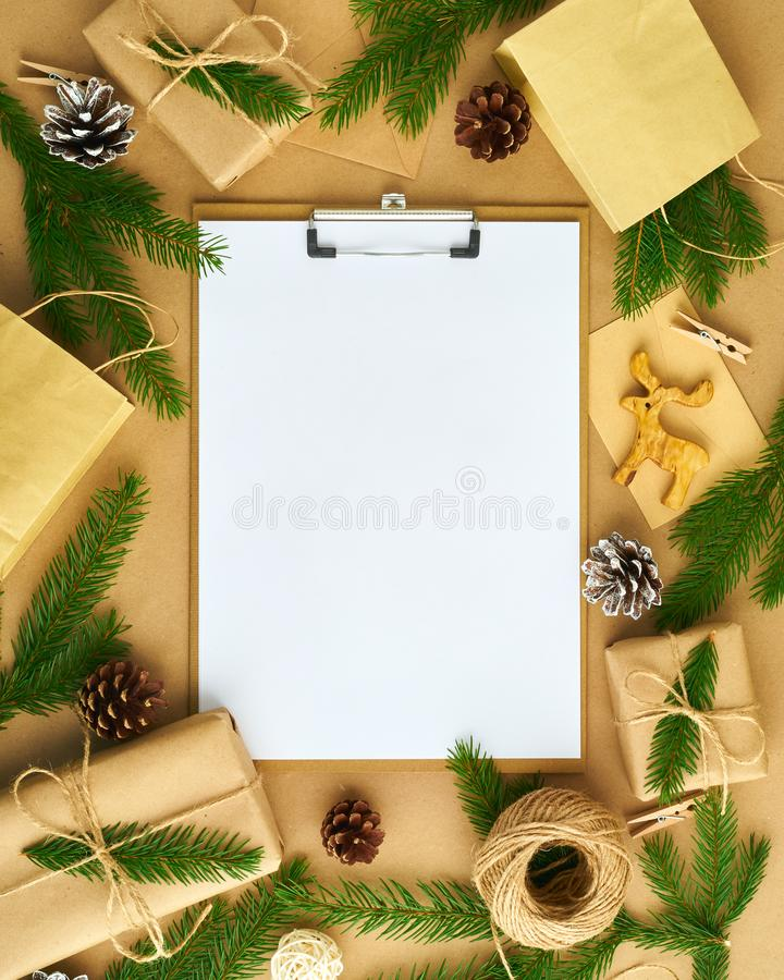 White open blank on clipboard and Christmas decoration lying on beige craft paper background, flat lay, copyspace. Hand crafted, stock photos