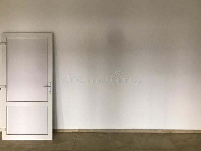 A white plastic door stands on a white plastered wall. indoor renovation. installation of doorways, external and internal. Decoration. repair door on a brown royalty free stock images