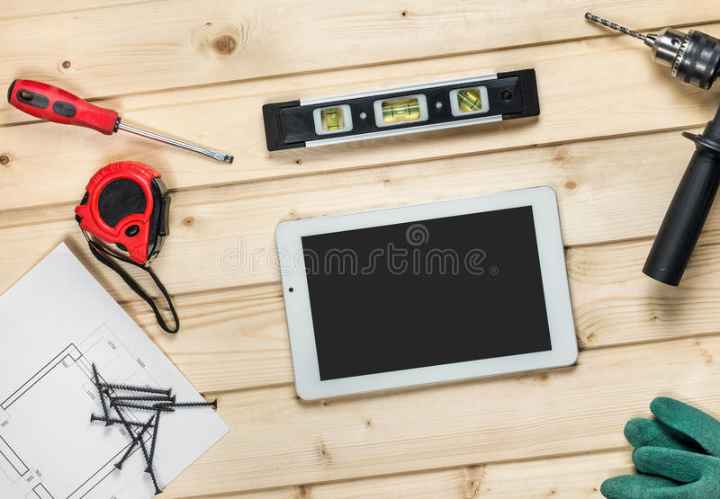 White tablet and set of hand construction tools to repair on a wooden surface: drill, pliers, self-tapping screws stock photography