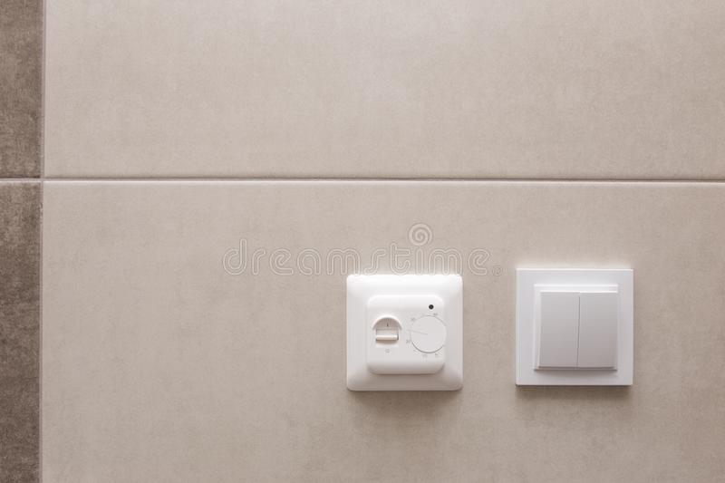 White temperature controller of a warm floor on a gray wall. stock image