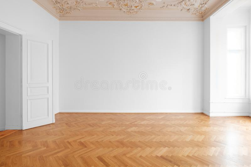 White wall background in empty apartment room , flat with wooden floor and stucco ceiling.  royalty free stock images