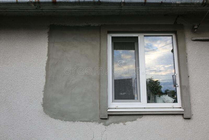 Window in the maintenance decorating process. Concrete on the grey house.  stock image