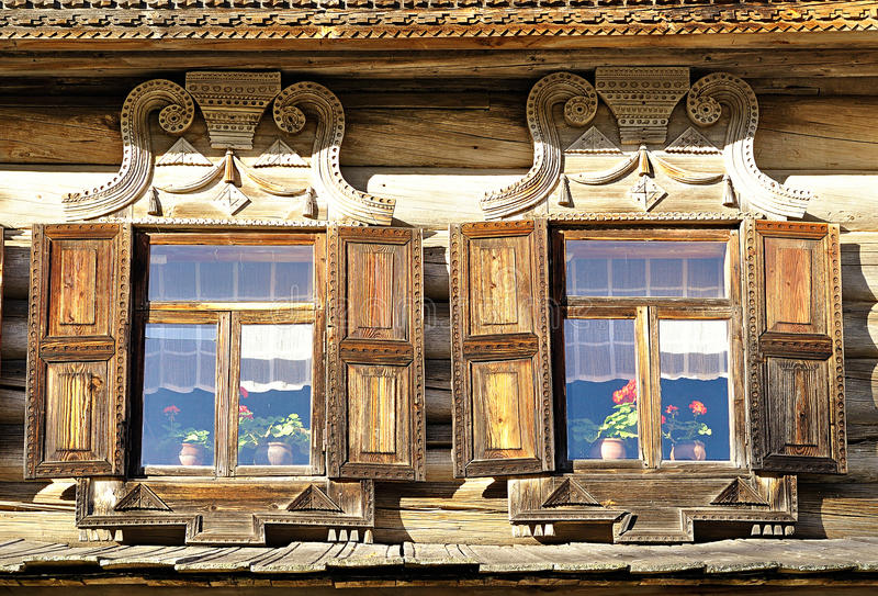 Windows of wooden Russian house built in traditional Russian country style. The windows of the wooden Russian house built in traditional Russian country style royalty free stock image