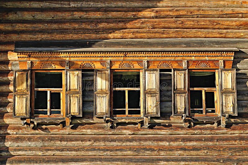 Windows of wooden traditional Russian house built in Russian country style. Three windows of the wooden traditional Russian house built in Russian country style royalty free stock photo
